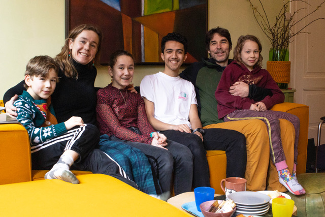 Judith, John, hun 3 kinderen en gast Amran zitten op de bank